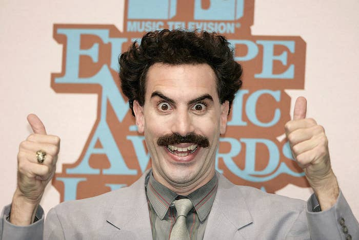 Sacha Baron Cohen as Borat giving two thumbs up with a deranged smile on his face