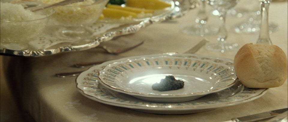 A delicate dollop of Beluga caviar on a plate, with a dinner roll on the side