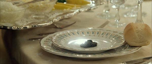 Sesendok lembut kaviar Beluga di atas piring, dengan gulungan makan malam di sampingnya
