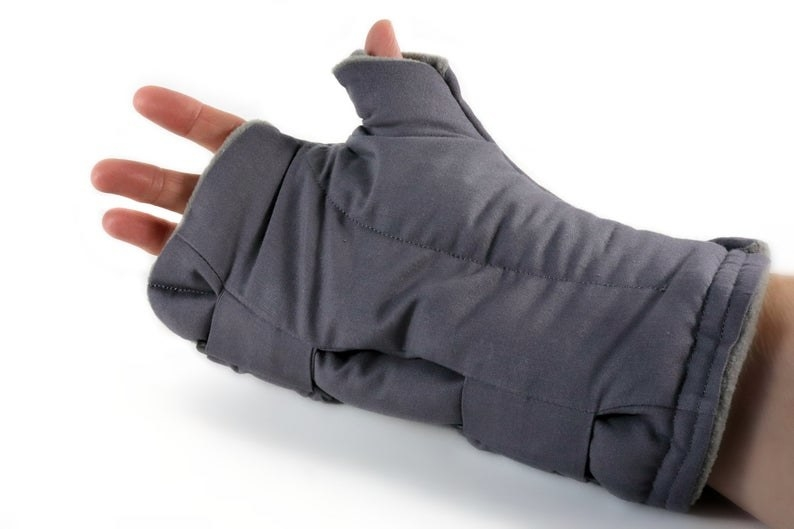 Model in a gray wrap covering their hand to below their wrist with fingers exposed