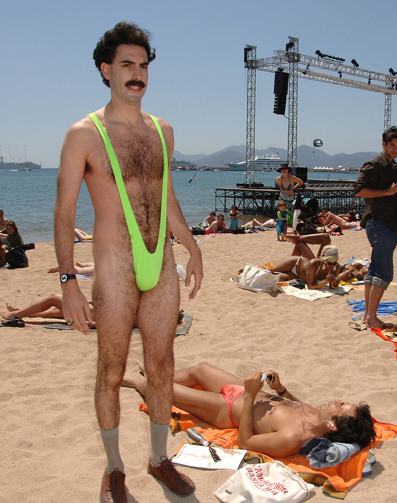 Borat on a beach in bathing suit that leaves very little to the imagination and shoes with socks on
