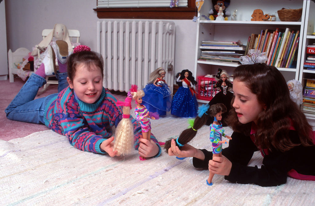 two girls playing with Barbies