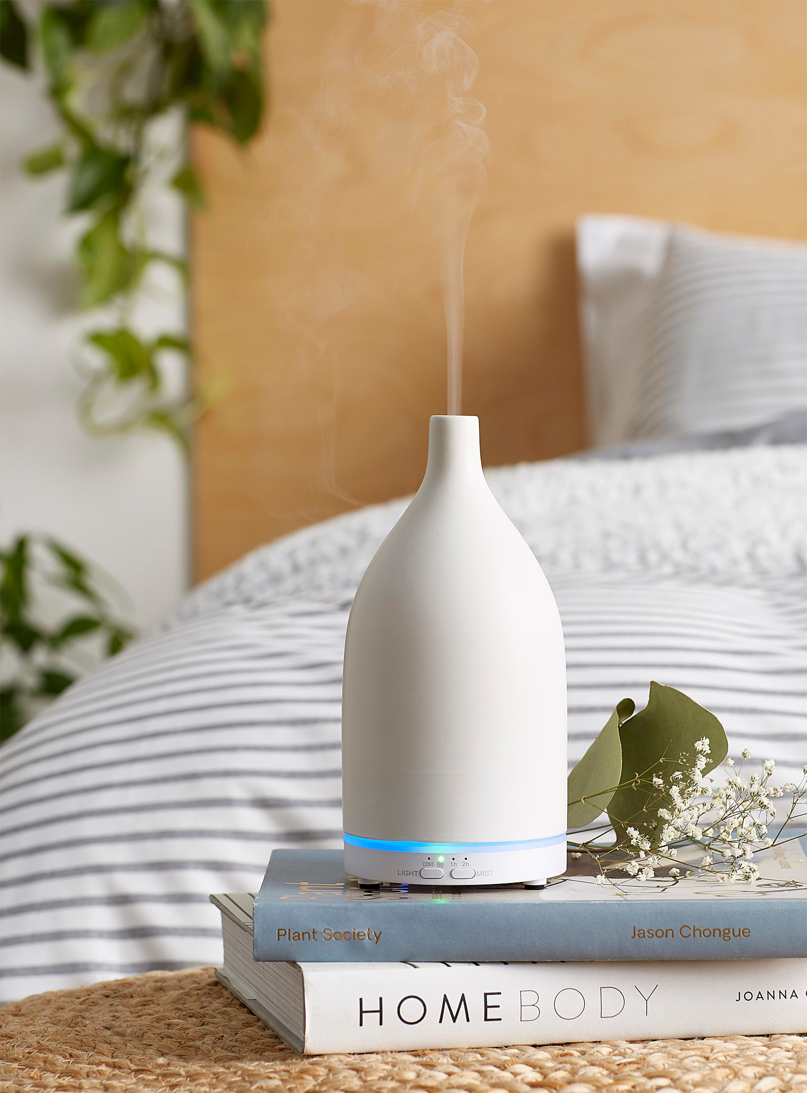 A ceramic diffuser that looks like a vase on a stack of books
