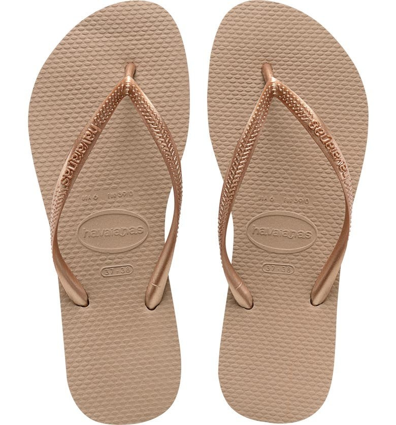 pair of golden flip flops with skinny straps