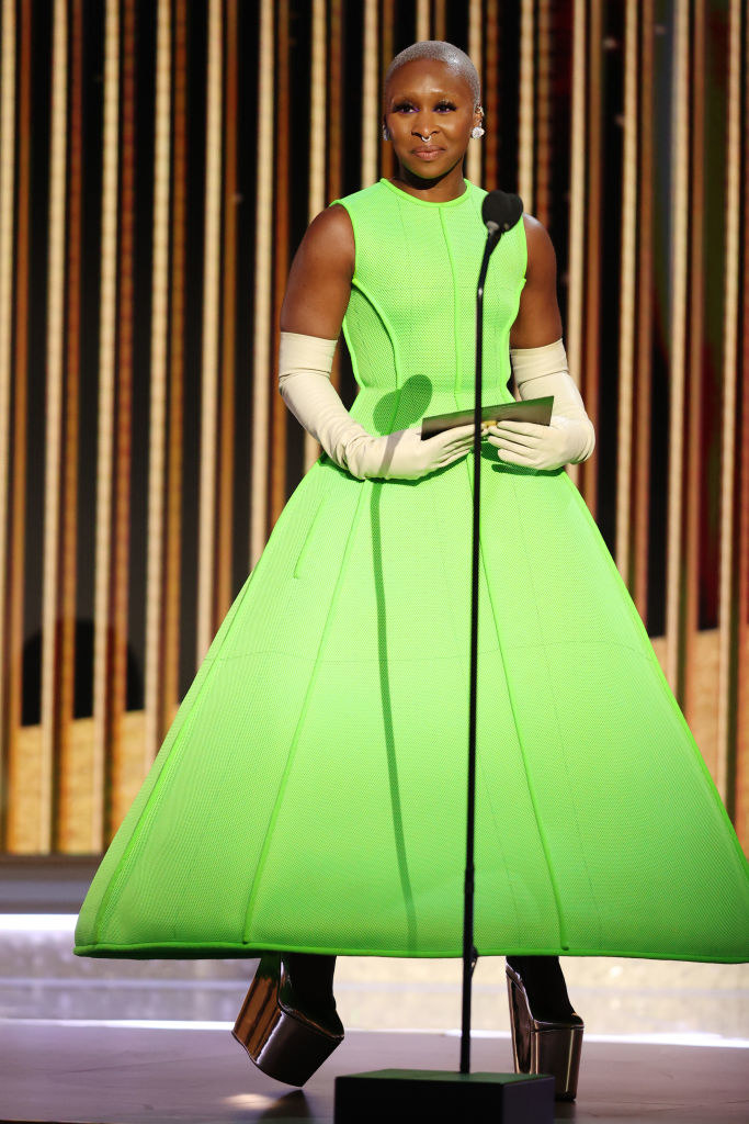 Cynthia presents in a neon green flared dress, gloves, and platform shoes