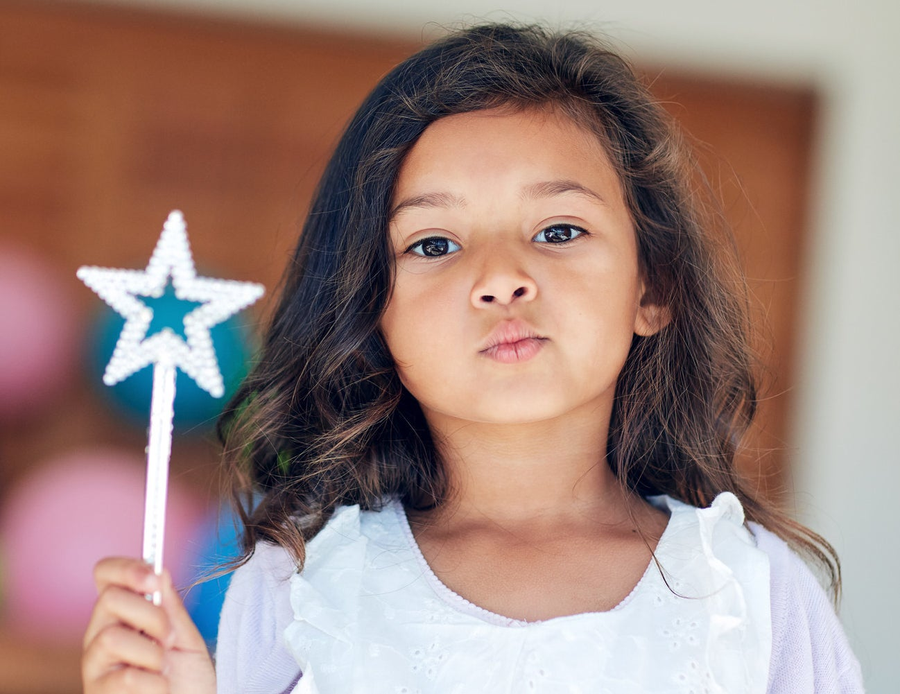 girl holding plastic wand with no expression
