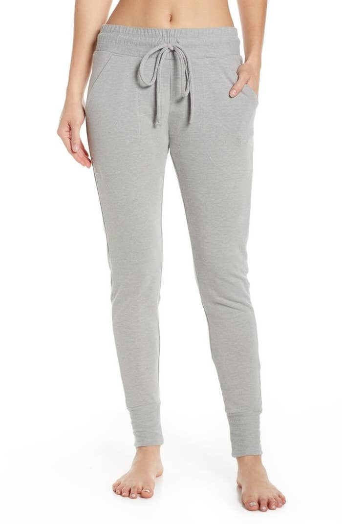 model wearing grey, tapered sweatpants with a jogger fit