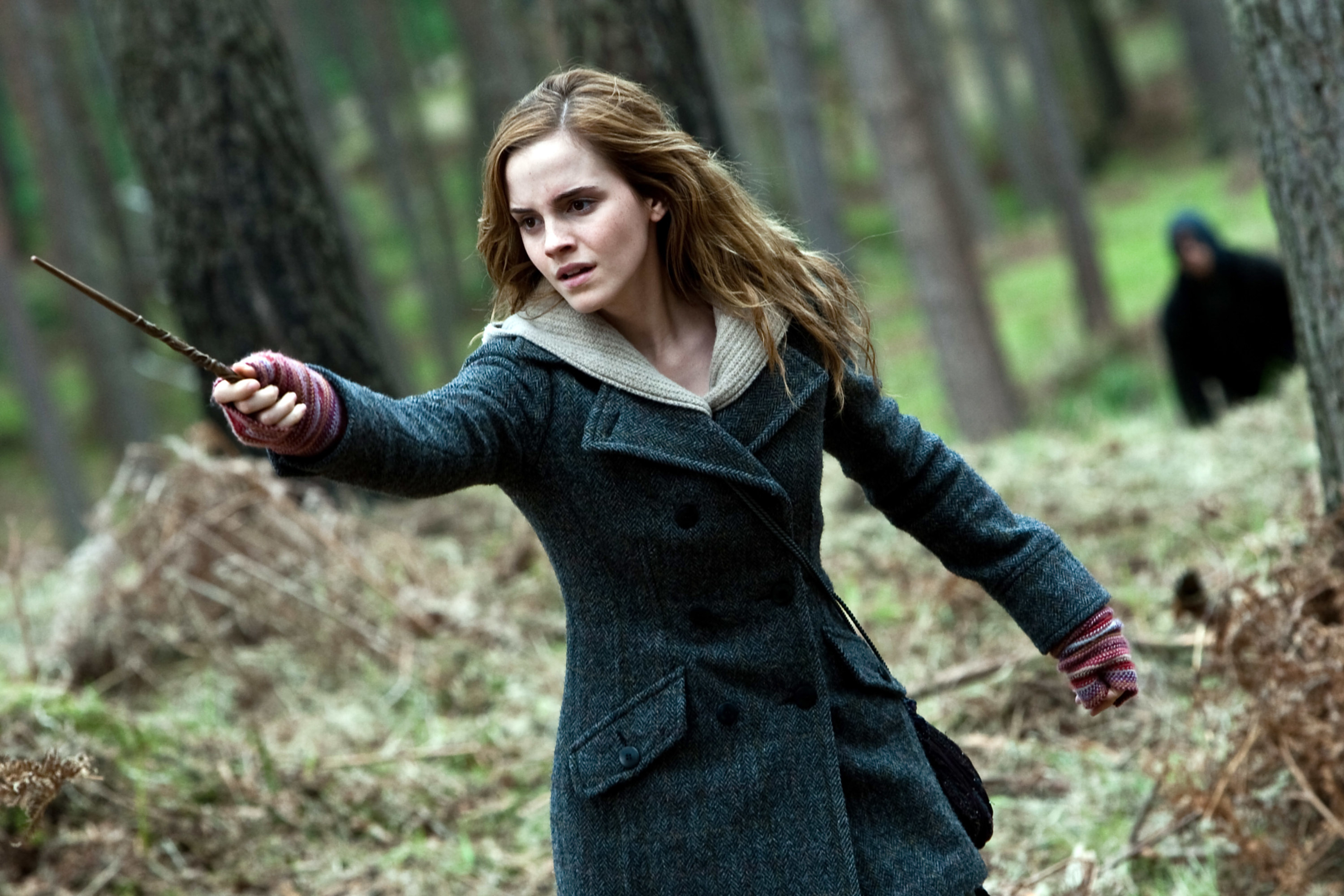Hermione holding her wand in the forest