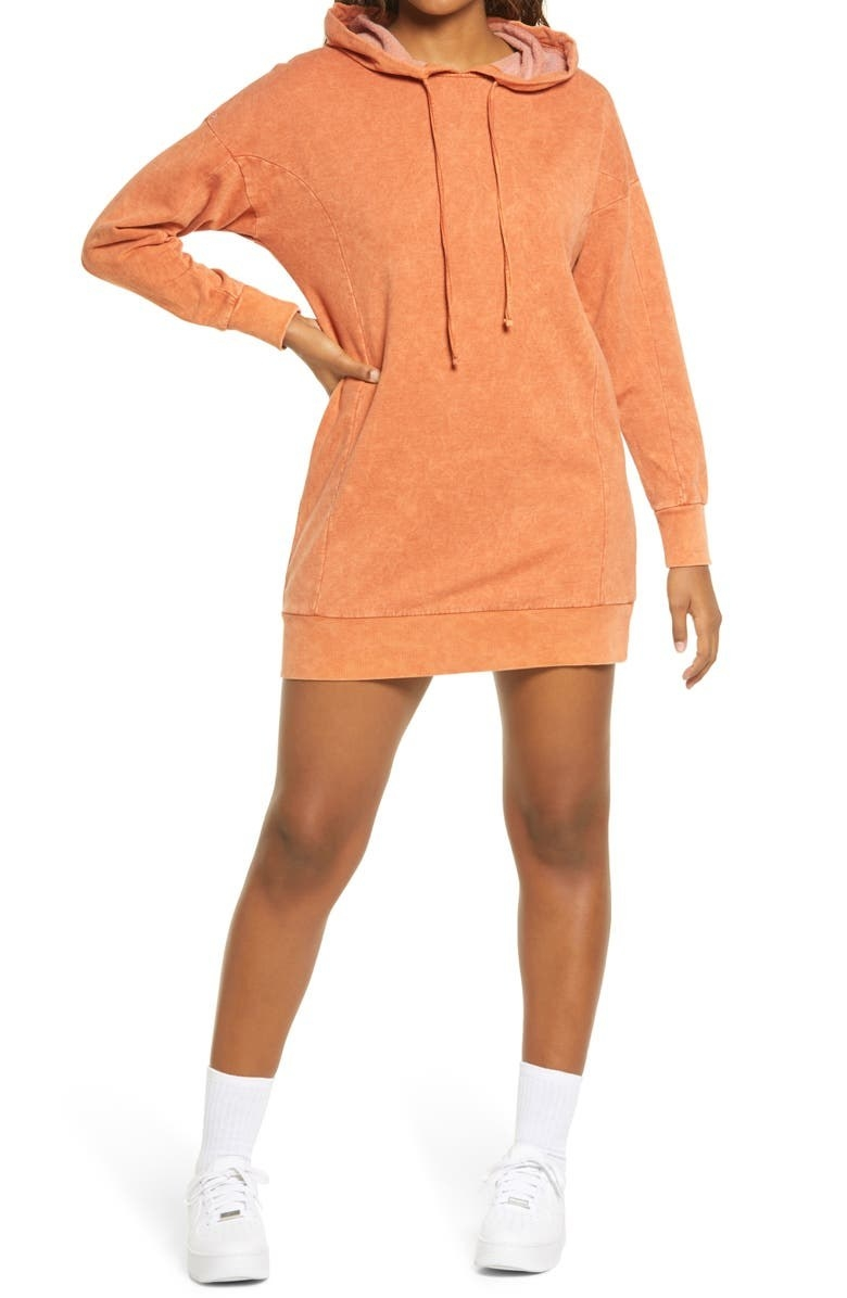 model wearing a orange sweatshirt dress