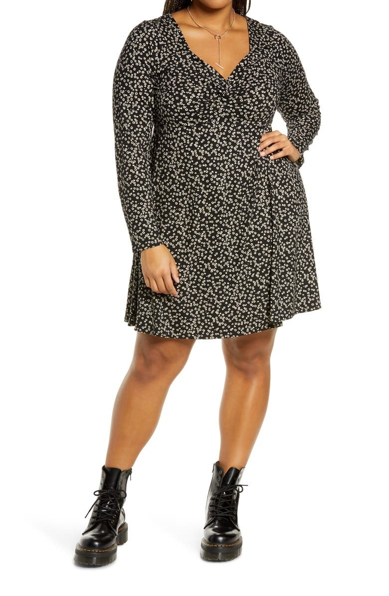 model wearing black floral longsleeved dress with black doc martens