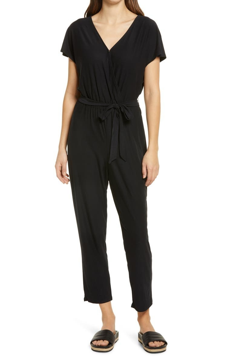 model wearing a black jumpsuit with a tie waist