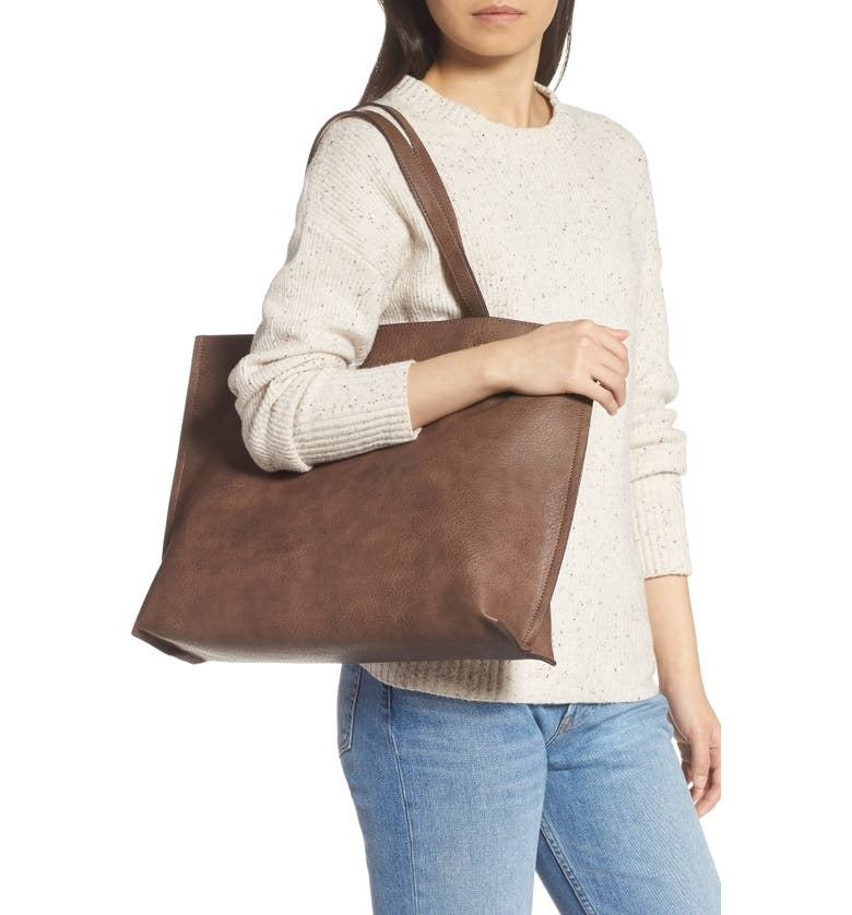 model carrying a brown faux leather bag on their shoulder