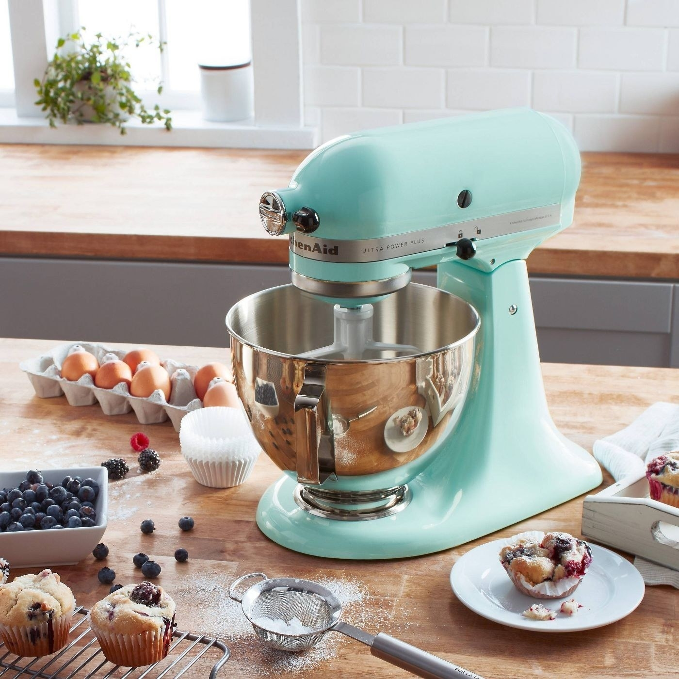 the aqua stand mixer on a counter with blueberry muffins