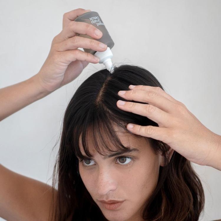 model applying the detox to her scalp