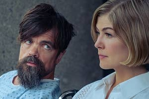 A man looks sadly at a woman with a stern face.