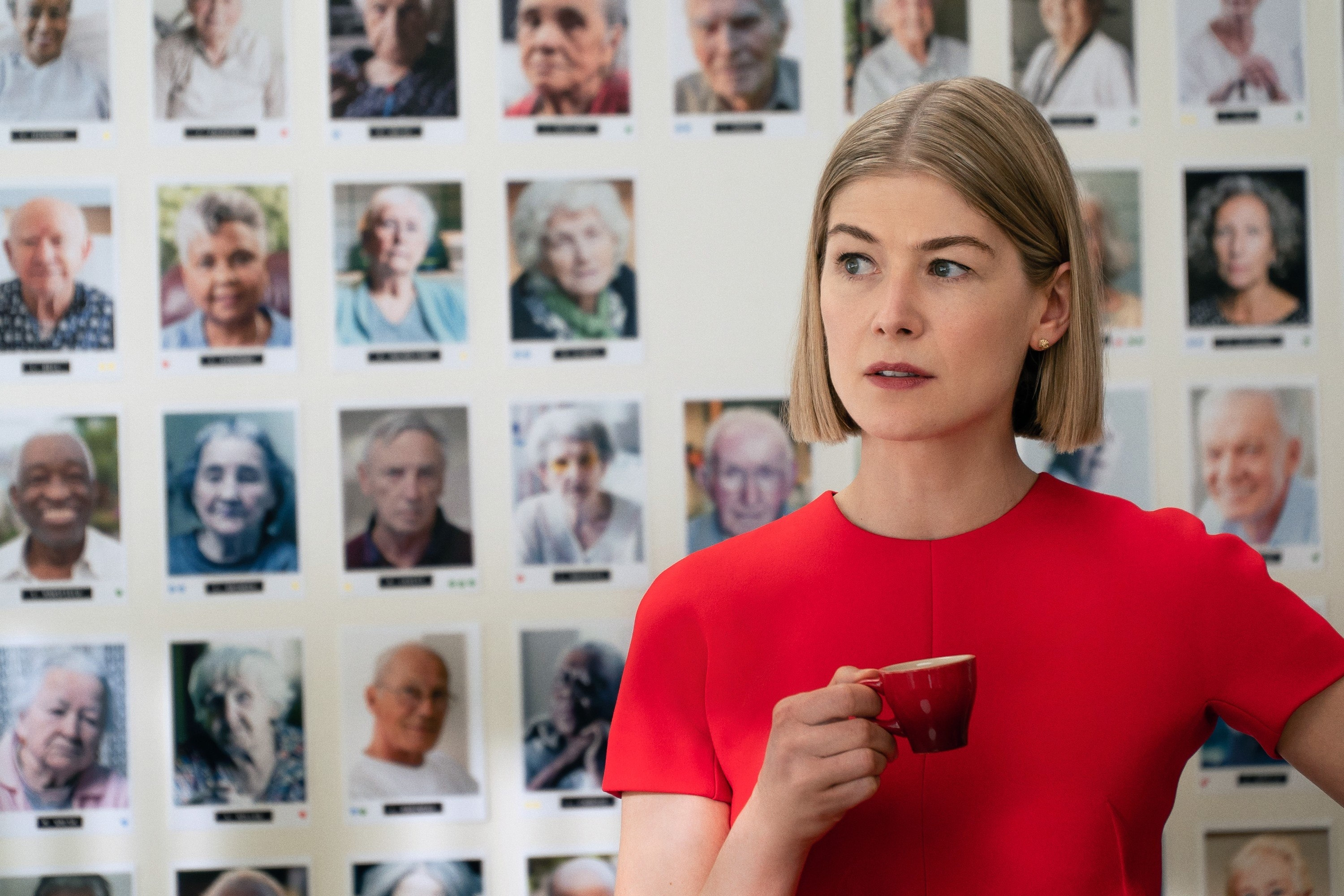 Rosamund holding a small cup with pictures of elderly people on a wall behind her in 'I Care a Lot'