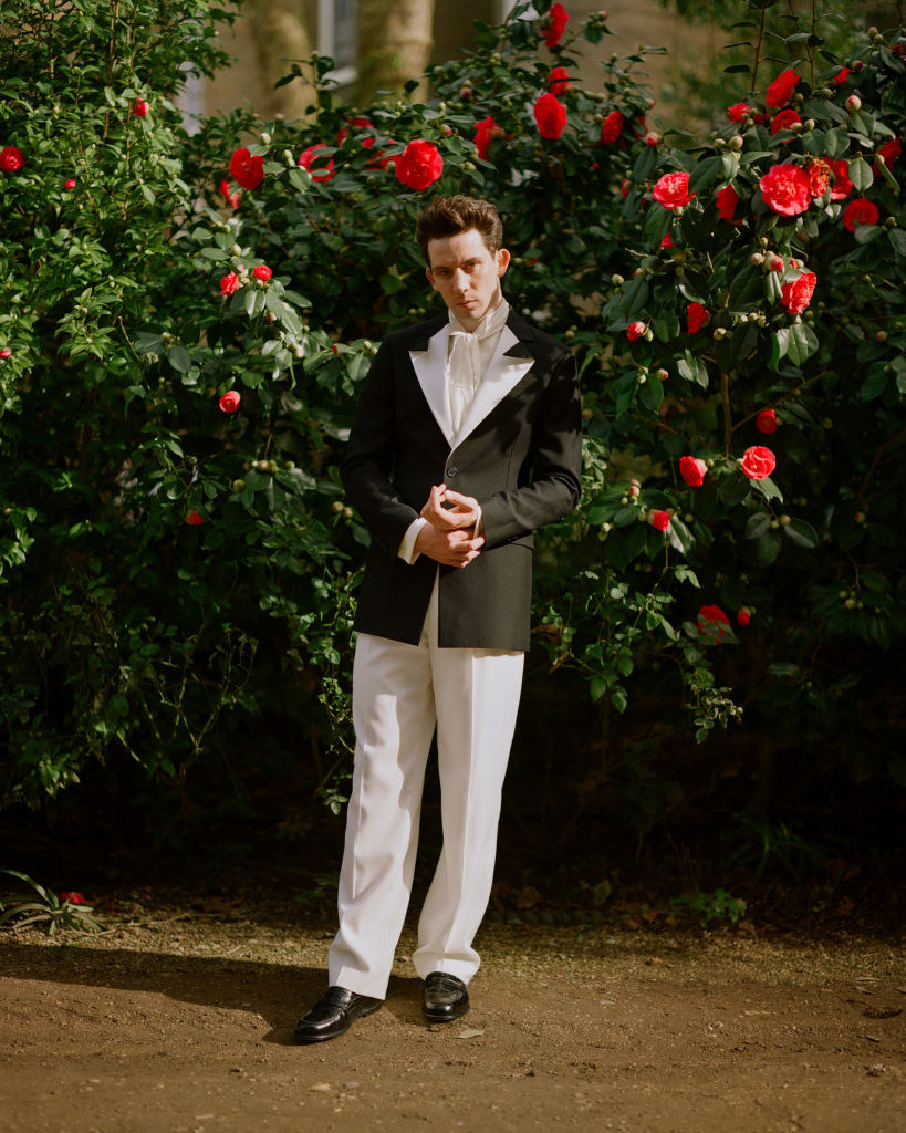 Josh poses on a dirt road in his suit and ascot