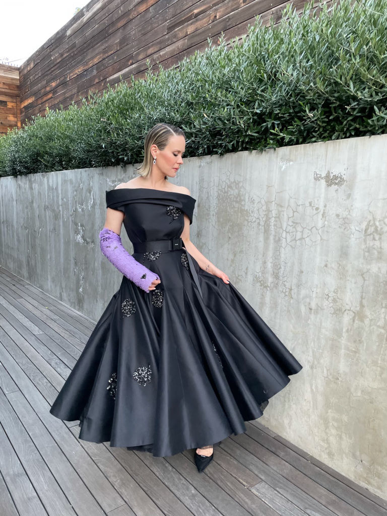 Sarah poses outside in an off-shoulder, belted dress and her arm cast