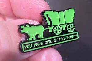 "hand holding a pin that looks like the 8-bit style of the Oregon Trail video game with ""you have died of dysentery"" on it"