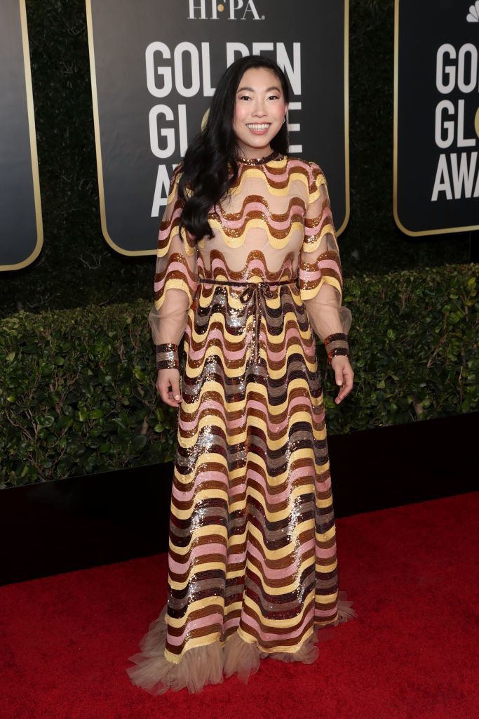 Awkwafina smiles in her striped gown