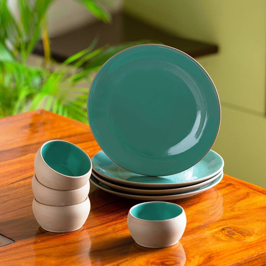 A set of turquoise plates on a table