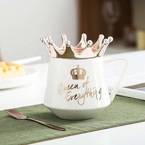 """A white mug with the words """"Queen of Everything"""" in golden. It has a golden crown around its rim."""