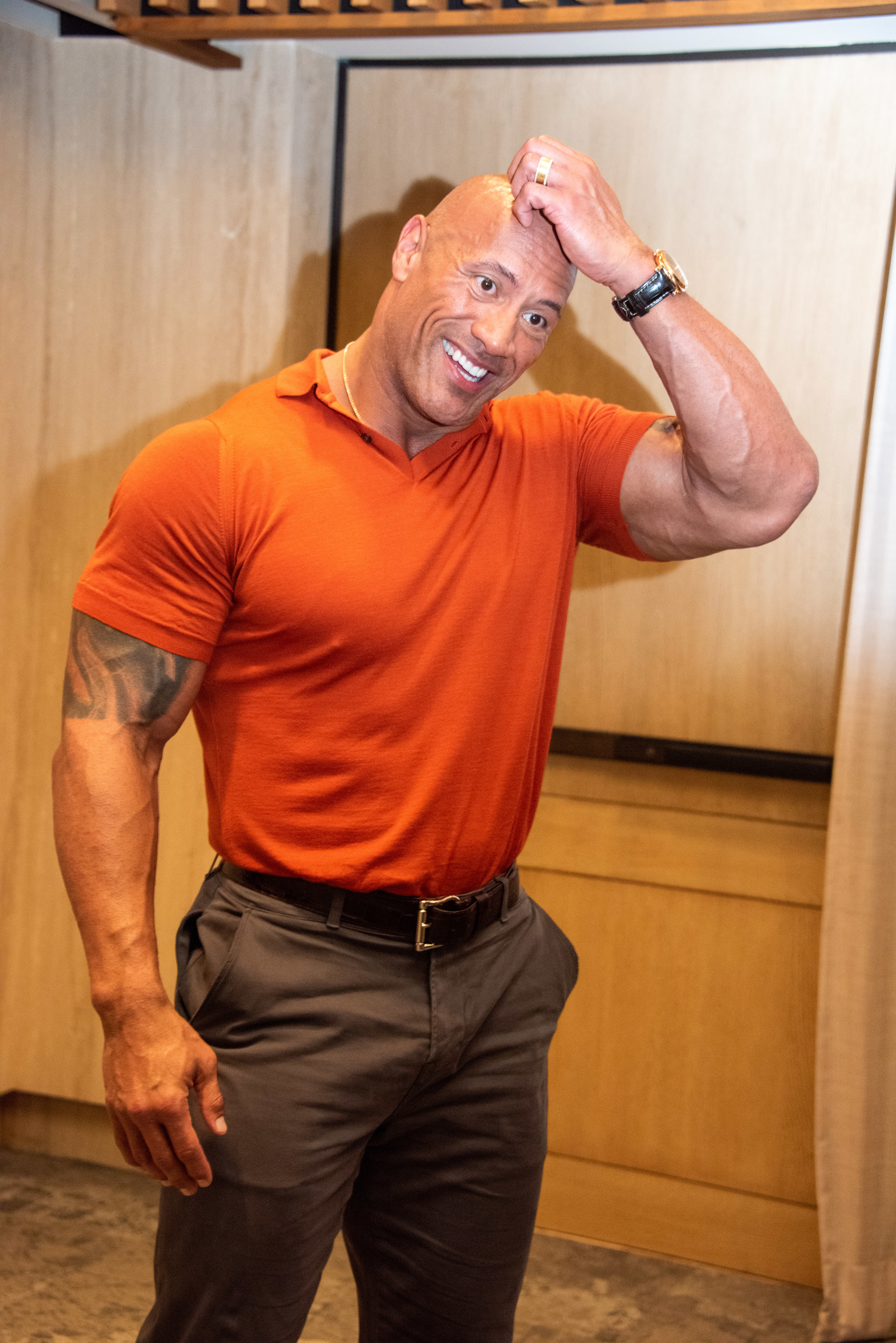 The Rock wearing a T-shirt and smiling and scratching his head