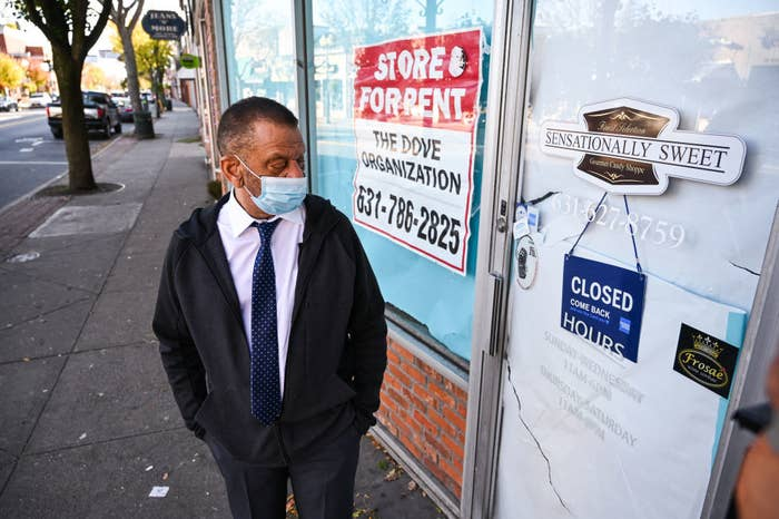 Man wearing a mask stands outside a shuttered business