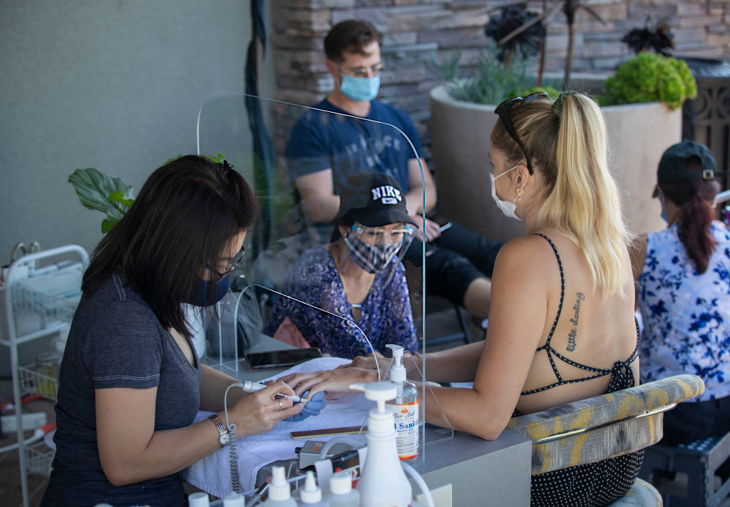 Nail technicians giving clients manicures at outdoor tables