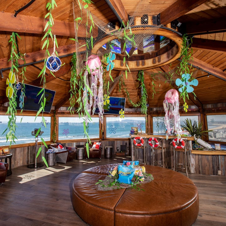 The living room which has several TVs hanging from the ceiling as well as seaweed, Spongebob plush toys and giant Jenga