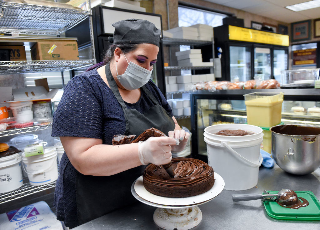 Masked worker frosting a cake in a restaurant kitchen