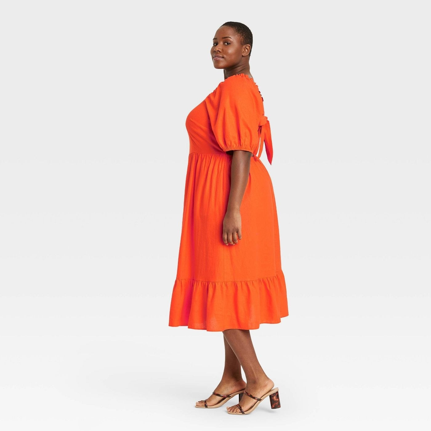 Model in orange dress with puff sleeves and an open back