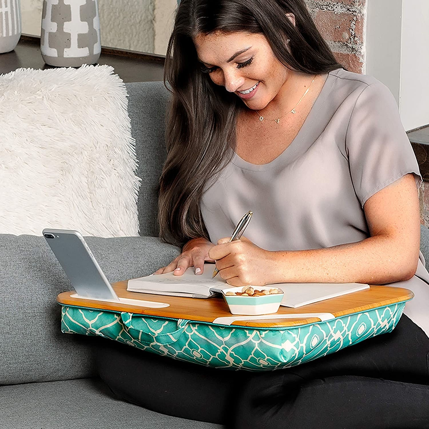 model with the light wood-like top and teal patterned fabric bottom on their lap with a book, phone, and snacks on it