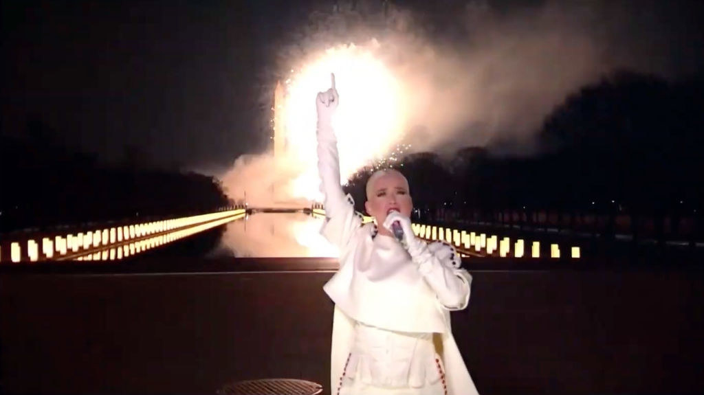 Katy pointing to the sky as she performs and fireworks pop off behind her