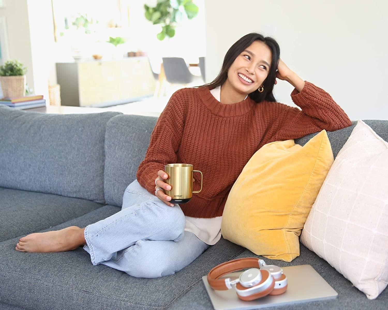 Model holding the gold mug