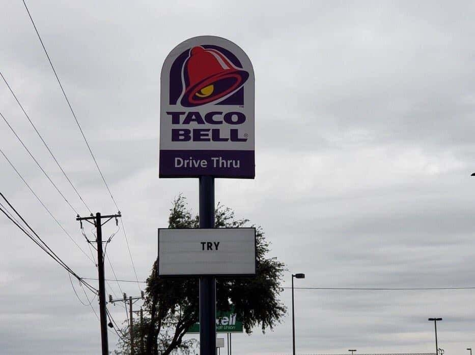 sign reading try below a Taco Bell logo