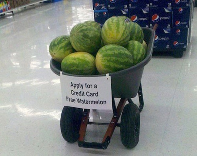 sign reading apply for a credit card free watermelon on a barrel of watermelons