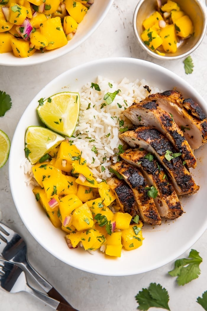 Jerk chicken plated with rice and mango salsa.