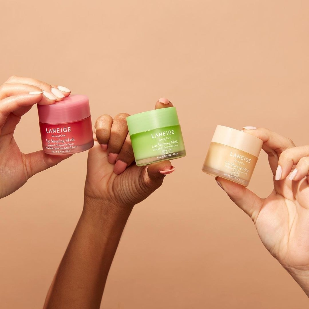 A trio of hands each holding a jar of the lip mask