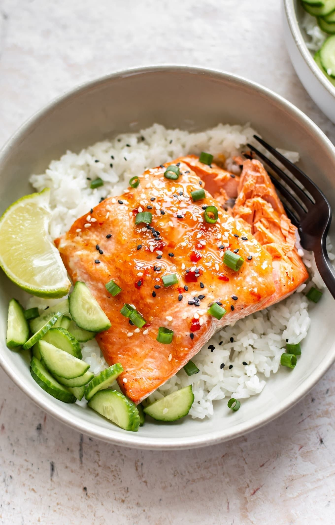 Chili salmon over rice with cucumbers.