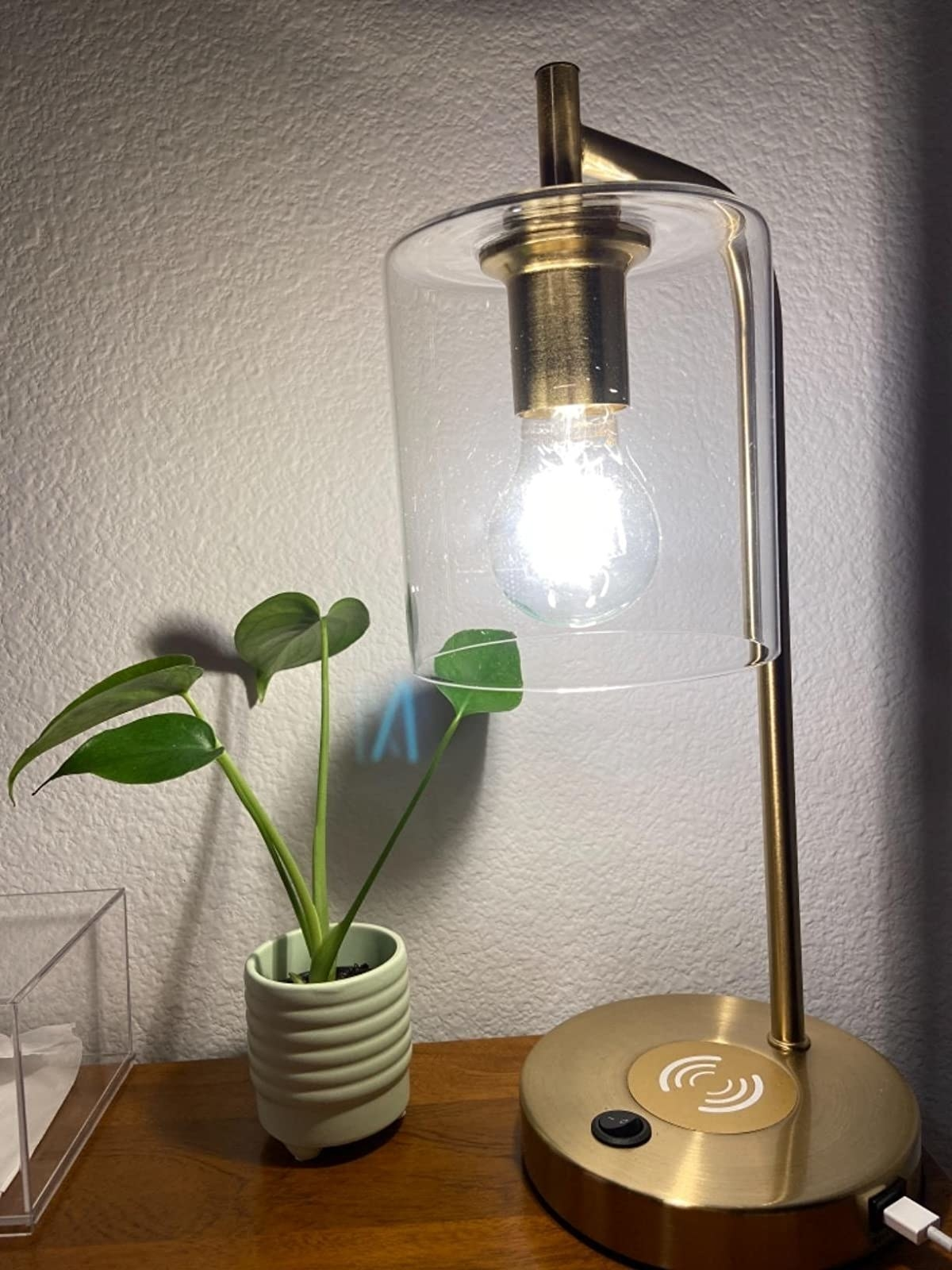 reviewer photo of the gold desk lamp with clear glass shade on a desk