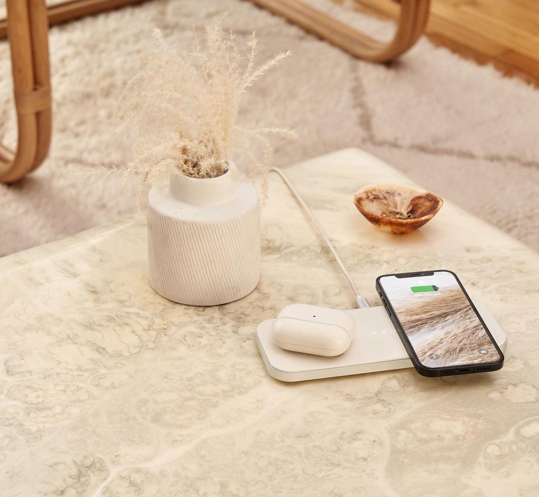long rectangular-shaped wireless charger in white with AirPods and an iPhone sitting on it