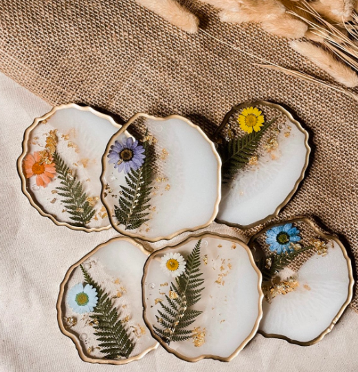 Several clear coasters with brushed white paint inside, gold leaf, fern leaves, and flower petals