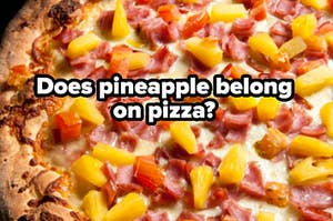 A pizza with ham and pineapple on top of it.