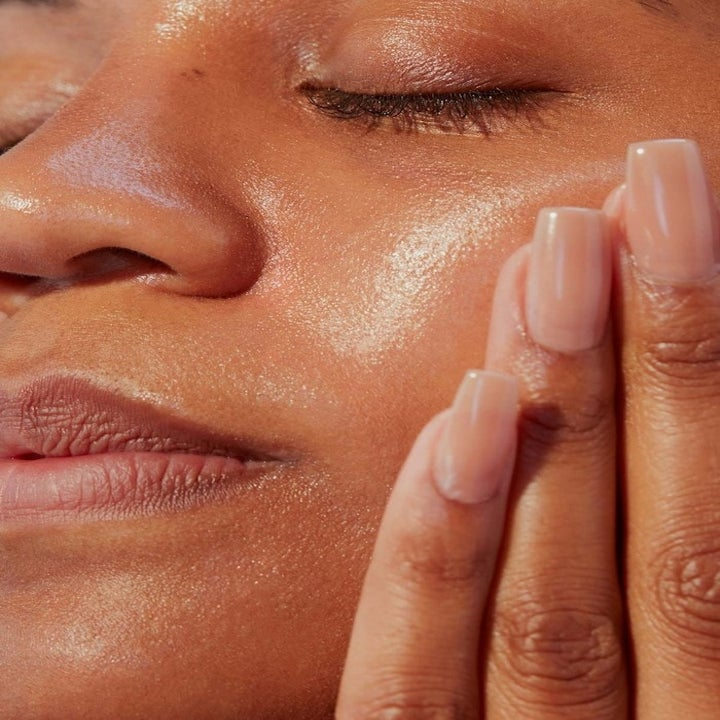 Model applying smooth moisturizer to face to leave glowing skin