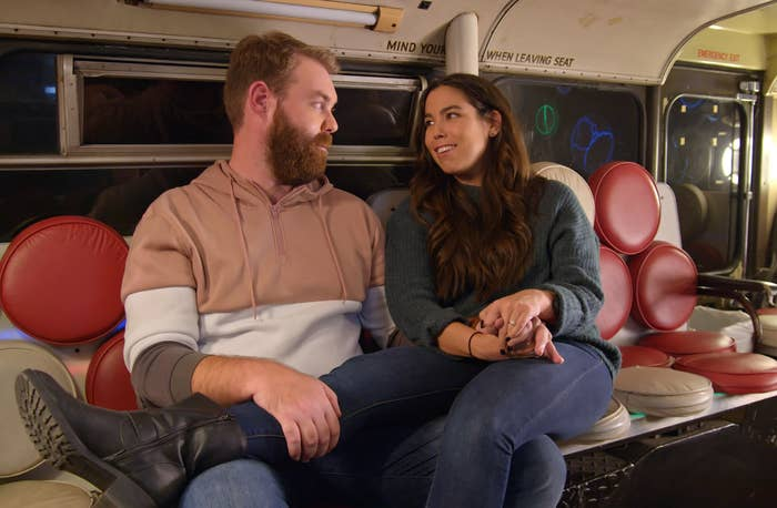 A woman sits next to a man with her legs over his lap