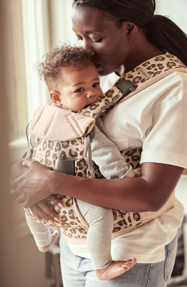 A model and baby with the BabyBjörn in Beige Leopard