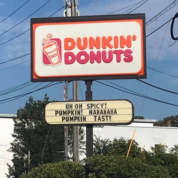 sign reading uh oh spicy pumpkin hahahaha pumpkin tasty below a Dunkin' Donuts logo