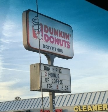sign reading now hiring 3 pounds of coffee for $19.99 below a Dunkin' Donuts logo