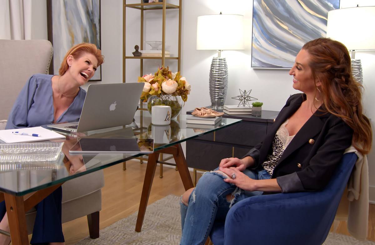 Two grinning women sit across a glass desk from one another in an office